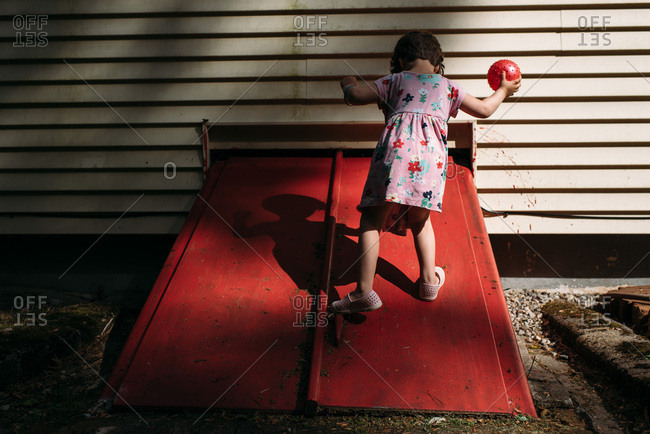 Little girl playing with a red ball in shadows by a red basement door