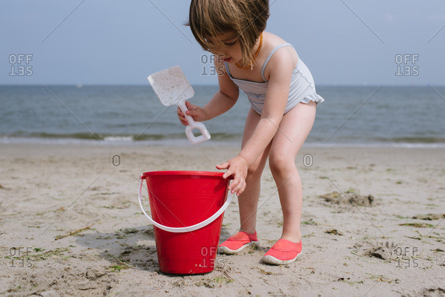 Young girl playing in sand at the beach with a red bucket and shovel
