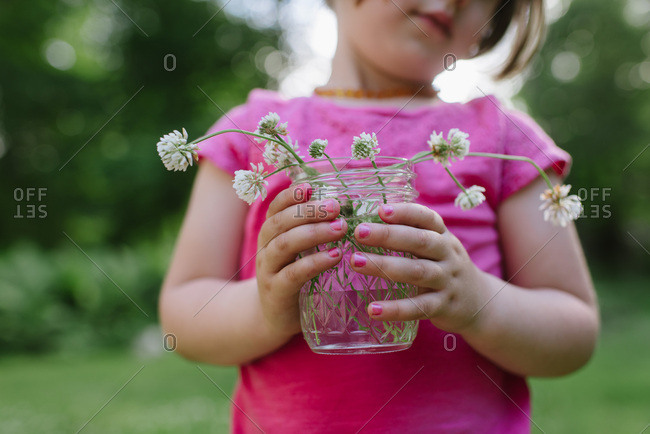 Little girl's hands with pink nail polish holding a mason jar of clover flowers