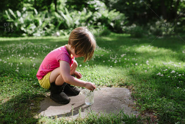 Girl picking clover flowers in a backyard