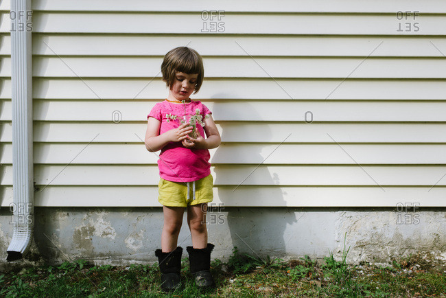 Little girl in pink shirt standing house holding a mason jar of flowers