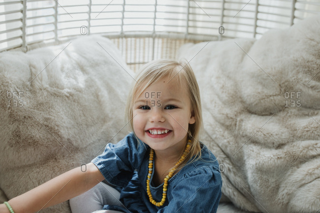 Blonde toddler girl smiling in a white swinging chair