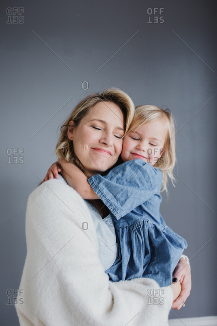 Portrait of a blonde mom and blonde toddler daughter hugging