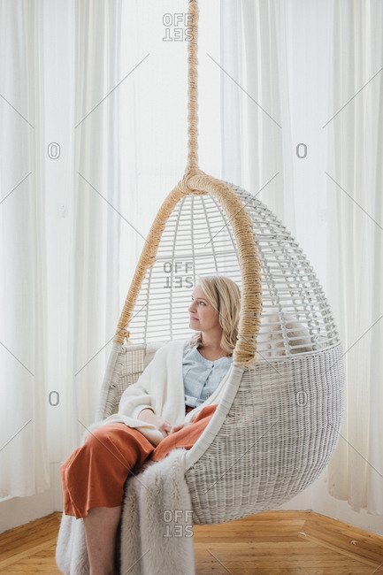 Blonde woman sitting in white swinging chair looking out window