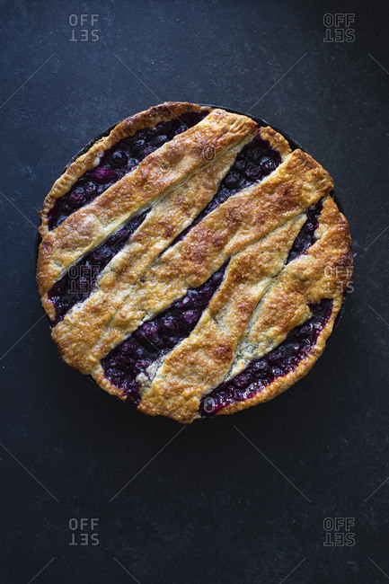 Cherry pie with a lattice and flaky crust shot on blue background