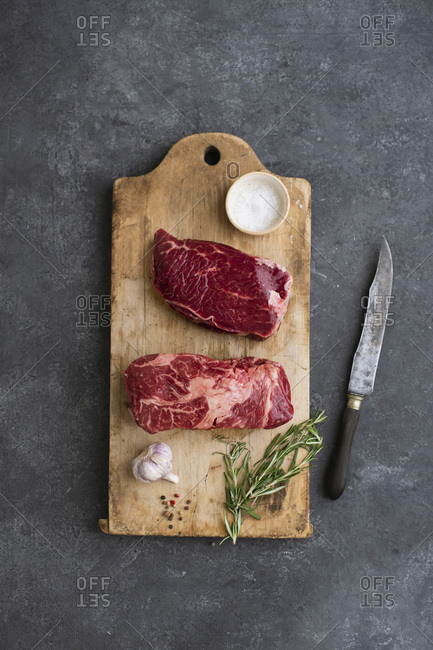 Raw black angus prime beef steak variety on vintage cutting board with rosemary, sea salt and spices