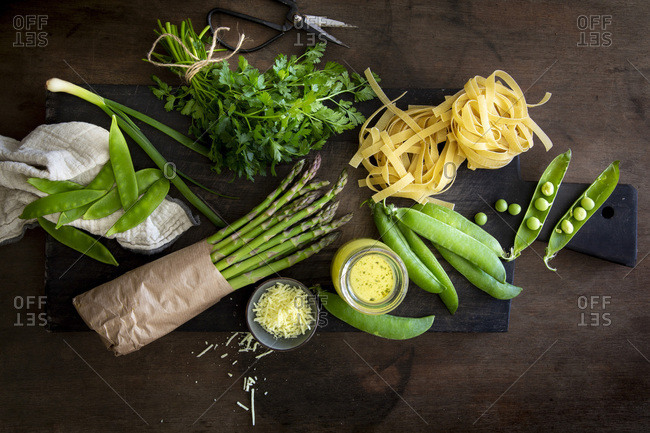 Tagliatelle, vegetables and herbs for home-made Pasta Primavera on black wooden board over wooden background