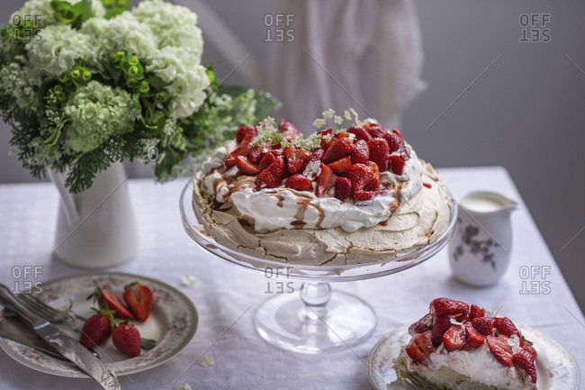Pavlova cake topped with whipped cream and fresh strawberries