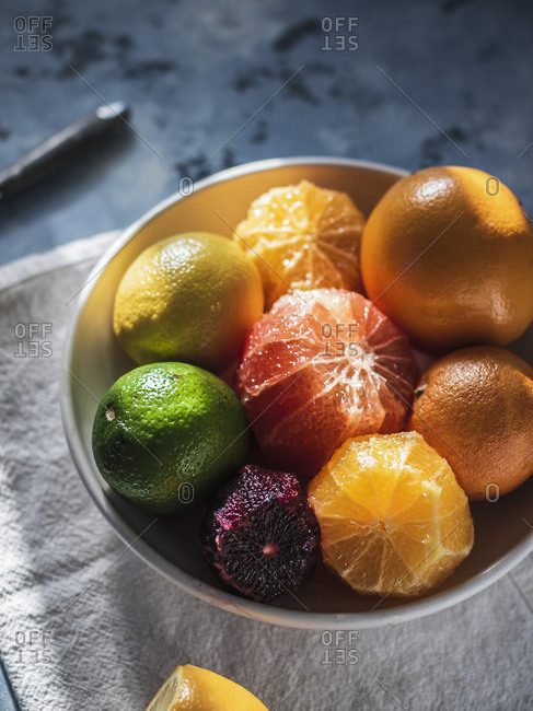 Citrus fruits in the bowl standing on the linen towel