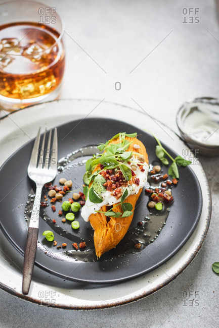 Whole baked sweet potato with sweet peas, lentils and bacon crumbs