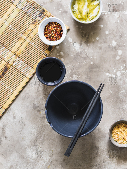 Top view on empty soup bowl, little condiment bowls and chopsticks.