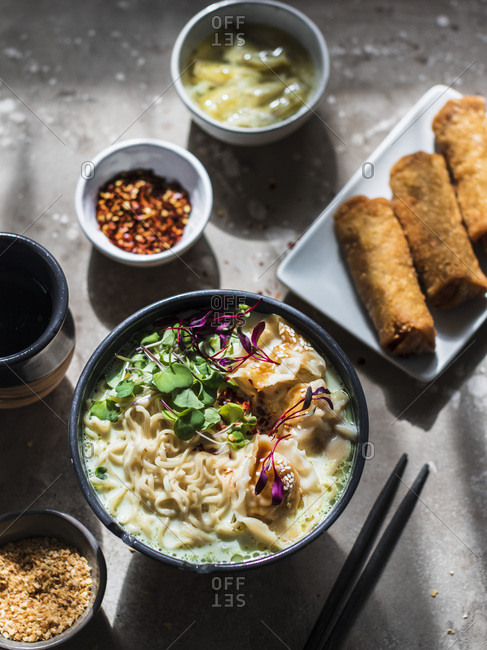 Asian dinner set: ramen noodle soup with pork dumplings, egg rolls and artichokes.
