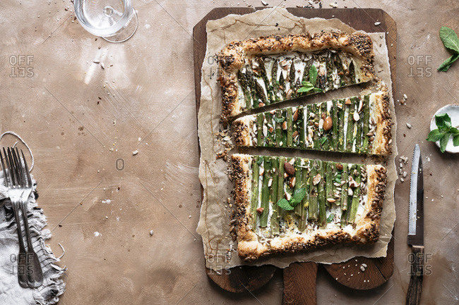 Asparagus tart on a brown board / with negative space