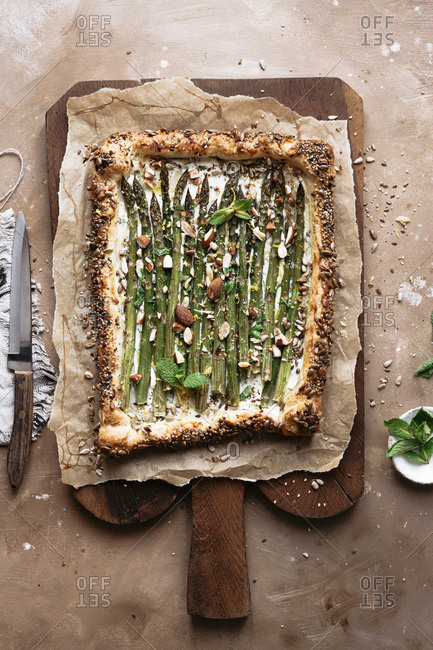 Asparagus tart onto parchment paper on a cutting board