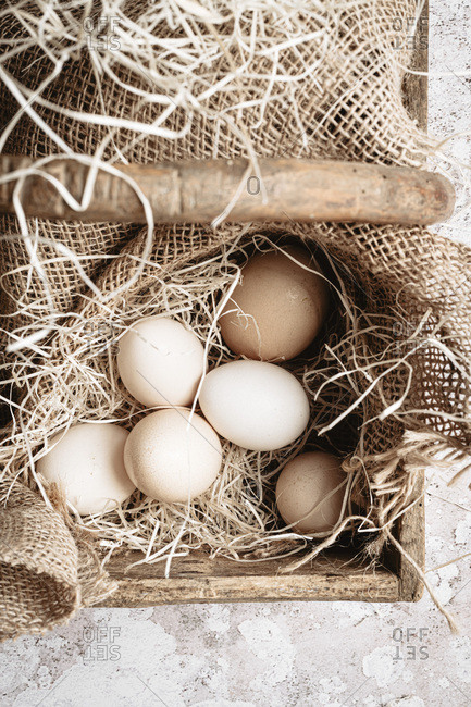 Six organic eggs into a wooden basket with straw