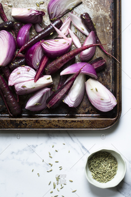 Purple onions and purple carrots on a metal tray, with olive oil and sprinkled with fennel seeds, ready for the oven. The surface is a marble tile and there is a small bowl of fennel seeds alongside.