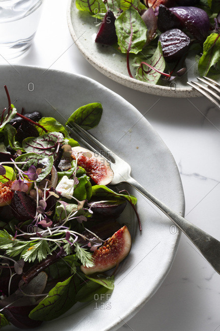 A salad of roasted beetroot, purple carrots and purple onions, with fresh figs, mixed leaves and micro herbs, dotted with feta cheese on two hand made plates. The surface is a marble tile and a glass of water and cutlery accompany.