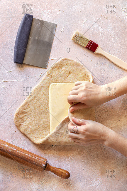 Female hands laminating puff pastry