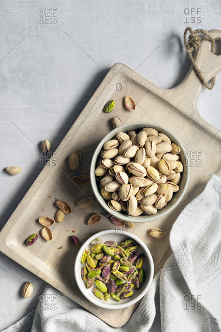 Roasted pistachio nuts in shells with a bowl of kernels.