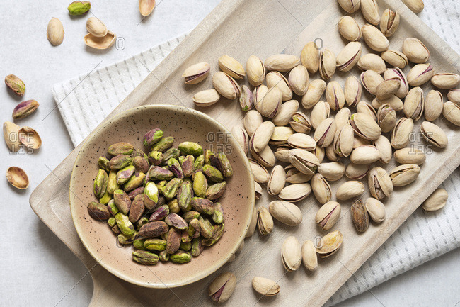 Roasted and salted pistachio nuts in shells with a bowl of kernels.