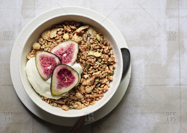 A bowl of muesli served with vanilla yoghurt and sliced figs.