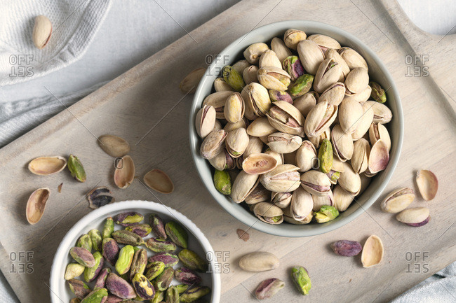 Roasted pistachio nuts in two bowls.