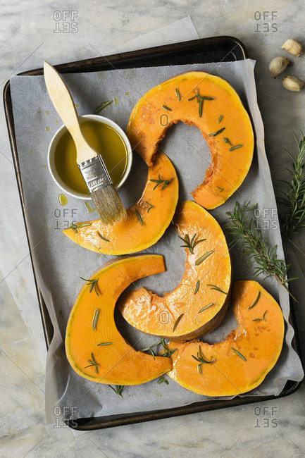 Sliced pumpkin on a baking tray covered with olive oil and rosemary.
