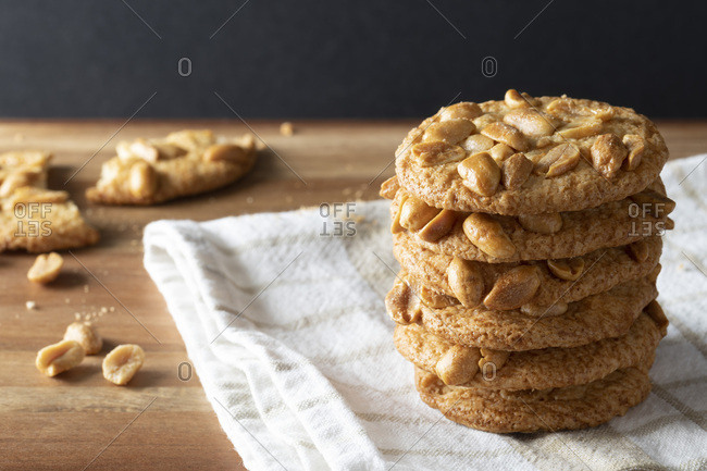 A stack of crisp peanut biscuits with a broken biscuit in the background.