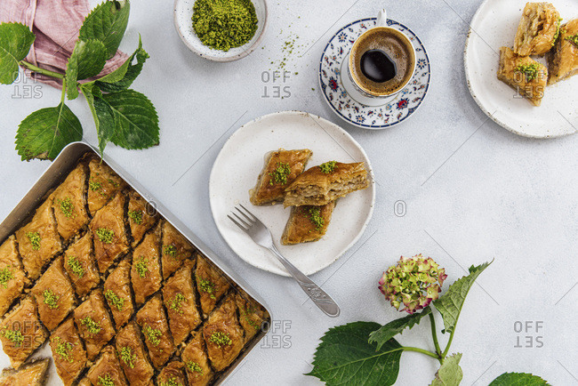Turkish coffee in a traditional Turkish coffee cup, two slices of baklava on a ceramic plate, a baking sheet full of newly made baklava with walnuts and pistachio on a grey background
