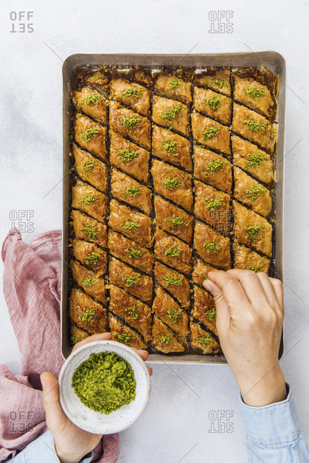Woman sprinkling pistachio over newly baked baklava