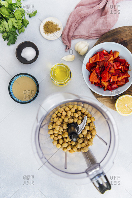 Cooked chickpeas in a blender, chopped roasted red peppers, tahini, olive oil and other hummus ingredients photographed on a grey background