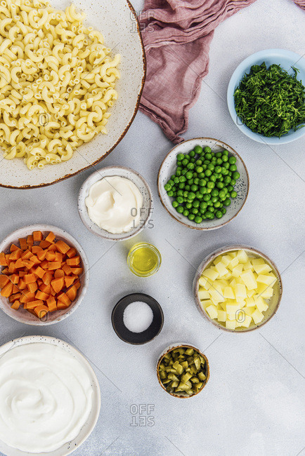 Macaroni salad ingredients photographed on a grey background