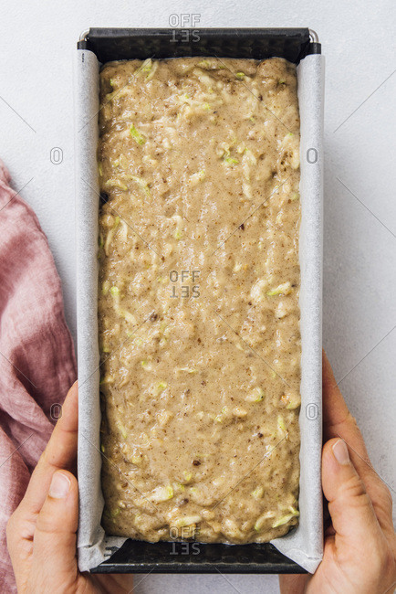 Woman holding vegan zucchini bread batter in a loaf pan