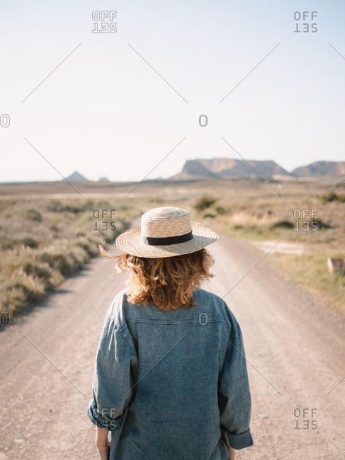 Blonde girl with straw hat wandering through the Bardenas desert