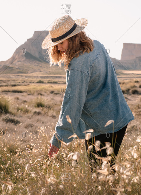 Blonde girl with straw hat exploring the desert