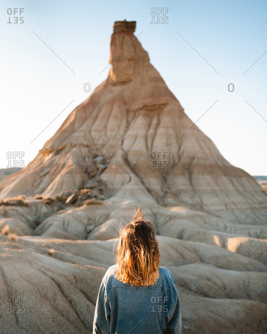 Young girl watching weird geologic formation and desert textures