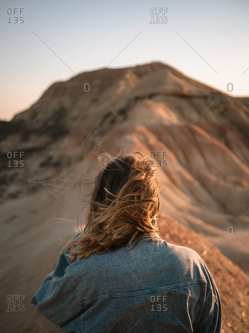 Young girl watching desert textures in sunset light