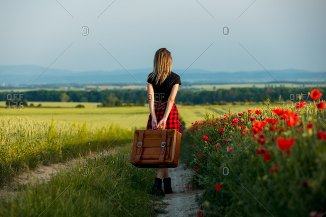 Young woman with suitcase on countryside road in summer time