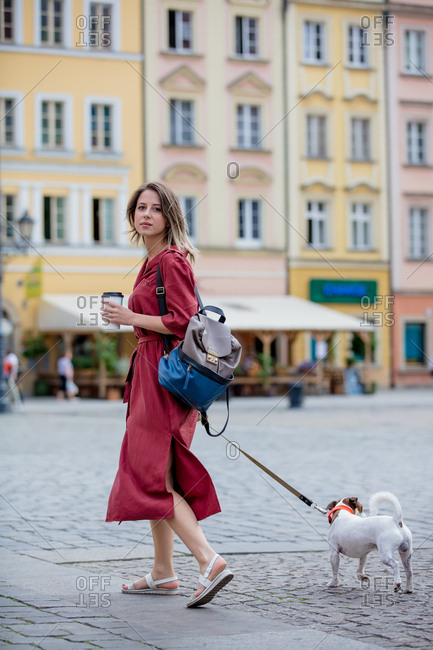 Young woman walking a dog in the city while drinking coffee