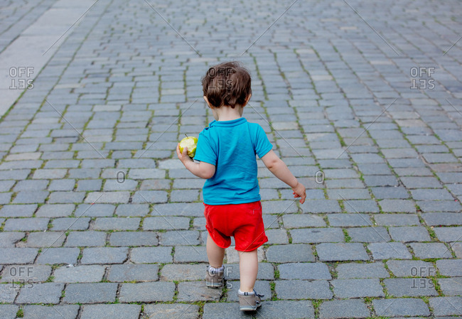 Little toddler boy walking on the pavement in the old town