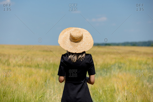 Female in black dress and hat stay in wheat field