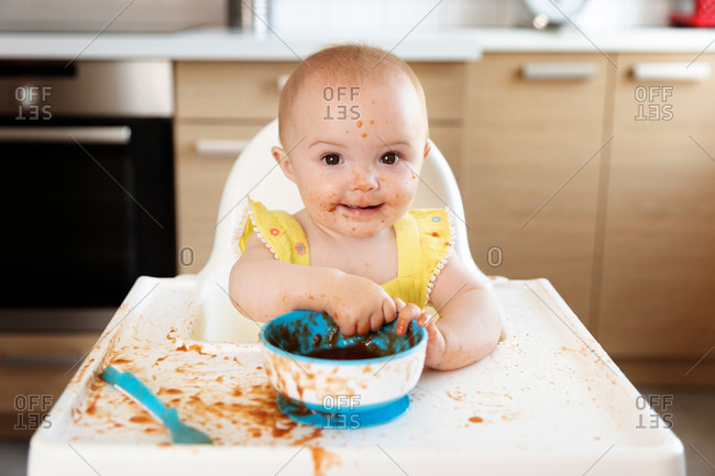 Cute baby in high chair making mess while eating puree