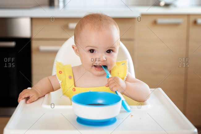 Cute baby in high chair eating with spoon