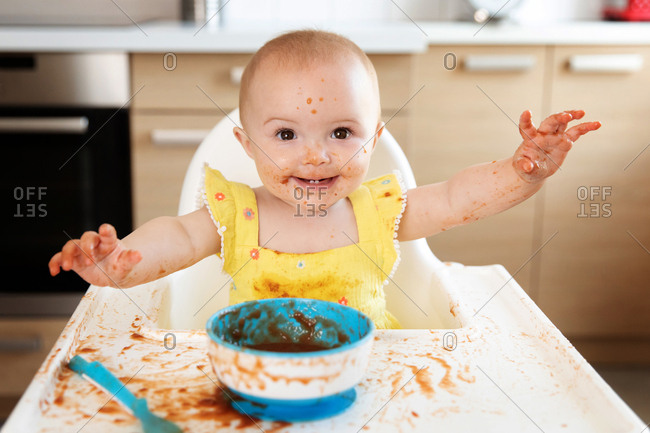 Happy baby in high chair making mess while eating puree
