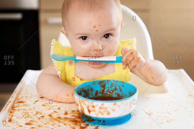 Funny messy baby in high chair with spoon in mouth