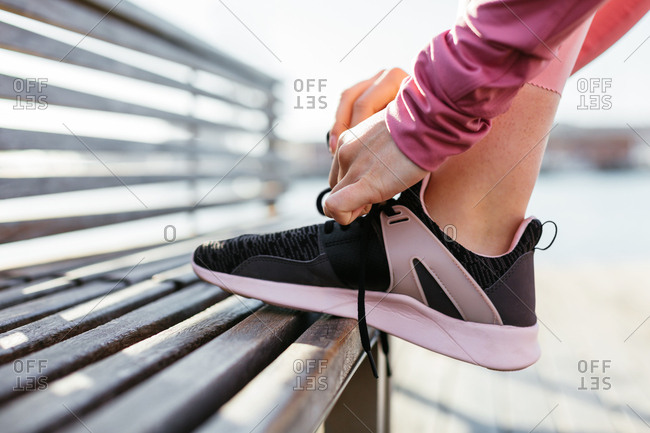 Woman lacing shoes in a bench in the street