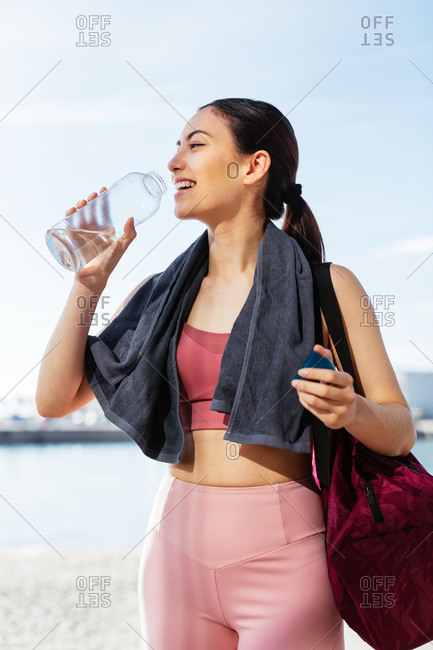 Young woman drinking water wearing sports clothes next to the water