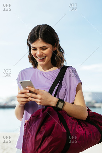 Young woman using  the phone wearing sports clothes next to the water