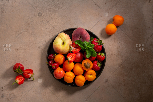 High angle view of fresh Summer berries and fruits on a plate.