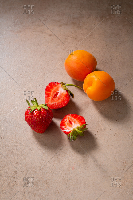 Top view of fresh summer strawberries and apricots.